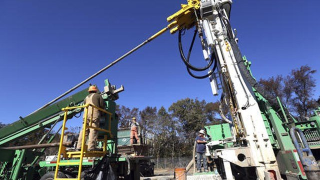 (Steve Earley/The Virginian-Pilot via AP). In a Nov. 17, 2016 photo, a drilling team for the U.S. Geological Survey adds 40 feet of drilling rod to a rig as they drill down to bedrock to install a land subsidence-measuring instrument.