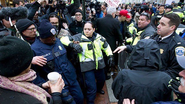 Police push back demonstrators attempting to block people entering a security checkpoint, Friday, Jan. 20, 2017, ahead of President-elect Donald Trump's inauguration in Washington. ( AP Photo/Jose Luis Magana)