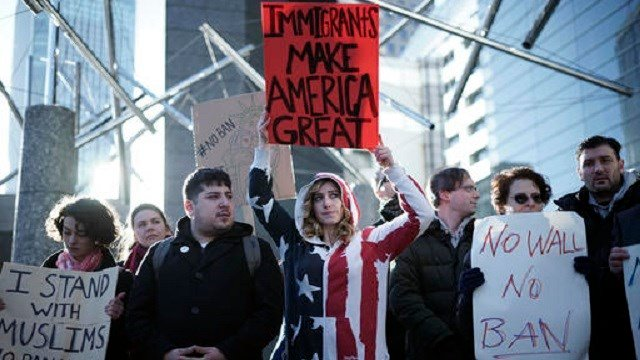 In this Tuesday, Jan. 31, 2017 photo, Americans and other expatriates gather to protest against U.S. President Donald Trump's recent travel ban to the U.S., outside of the U.S. Embassy in Tokyo. (AP Photo/Eugene Hoshiko, File)