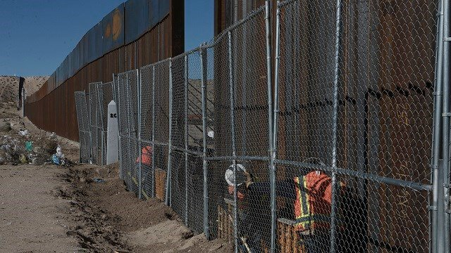 Workers continue work raising a taller fence in the Mexico-US border separating the towns of Anapra, Mexico and Sunland Park, New Mexico, Wednesday, Jan. 25, 2017.  (AP Photo/Christian Torres)