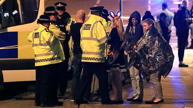 Emergency services personnel speak to people outside Manchester Arena after reports of an explosion at the venue during an Ariana Grande concert in Manchester. (AP Photo)