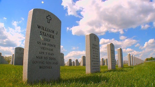 Leaving coins on the graves of the fallen