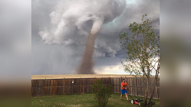 (Cecilia Wessels/The Canadian Press via AP) In this Friday, June 2, 2017, photo provided by Cecilia Wessels via The Canadian Press, Theunis Wessels mows his lawn at his home in Three Hills, Alberta, as a tornado swirls in the background.