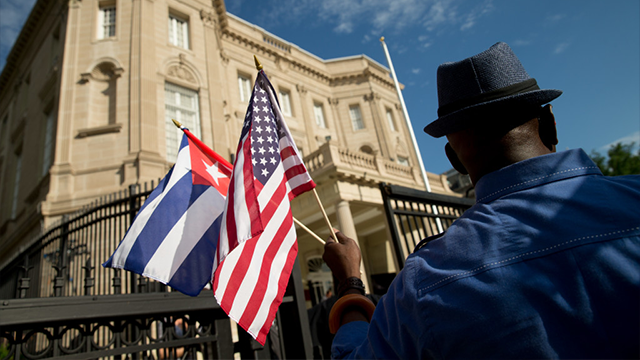Edwardo Clark, a Cuban-American, holds an American flag and a Cuban flag as he celebrates outside the new Cuban embassy. (The Associated Press)