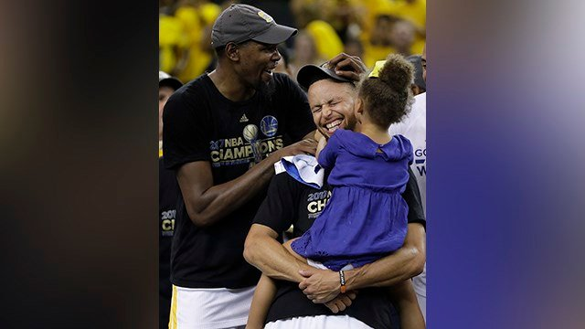 Golden State Warriors guard Stephen Curry, center, holds his daughter Riley as they celebrate with forward Kevin Durant, left, after Game 5 of basketball's NBA Finals against the Cleveland Cavaliers in Oakland, Calif. (AP Photo/Marcio Jose Sanchez)