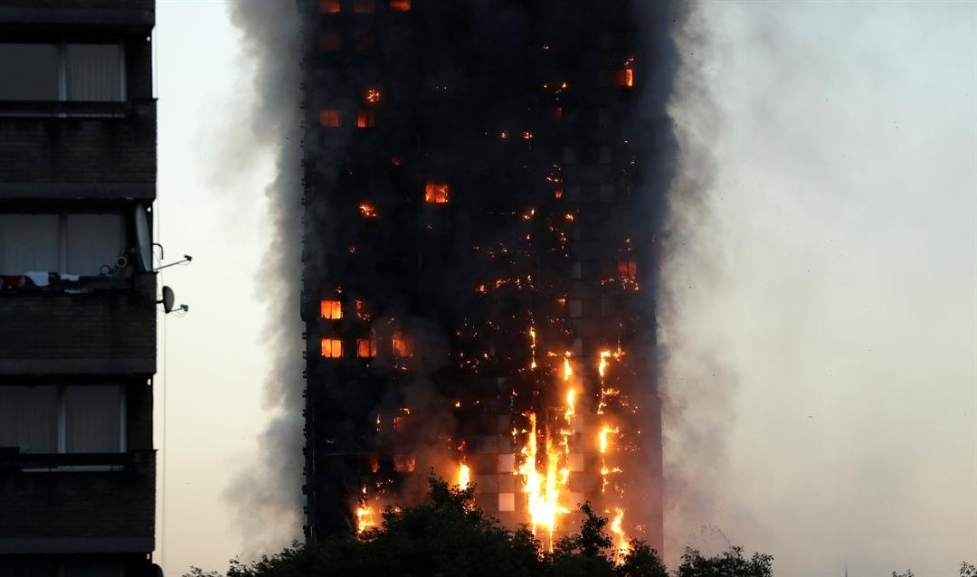 Smoke and flames rise from building on fire in London, Wednesday, June 14, 2017. Firefighters are battling a massive fire in an apartment high-rise in London. (AP Photo/Matt Dunham)