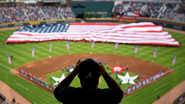 (AP Photo/David Goldman, File) FILE - In this May 20, 2017, file photo, a spectator takes a photo of a United States flag as it is unveiled for the national anthem as part of Military Appreciation Day before a baseball game between the Atlanta Braves...