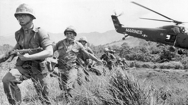 In this April 28, 1965 file photo, U.S. Marine infantry stream into a suspected Viet Cong village near Da Nang in Vietnam during the Vietnamese war. Filmmaker Ken Burns said he hopes his 10-part documentary about the War, which begins Sept. 17, 2017.