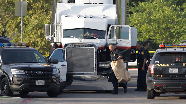 San Antonio police officers investigate the scene where eight people were found dead in a tractor-trailer loaded with at least 30 others outside a Walmart store in stifling summer heat. (AP Photo/Eric Gay)