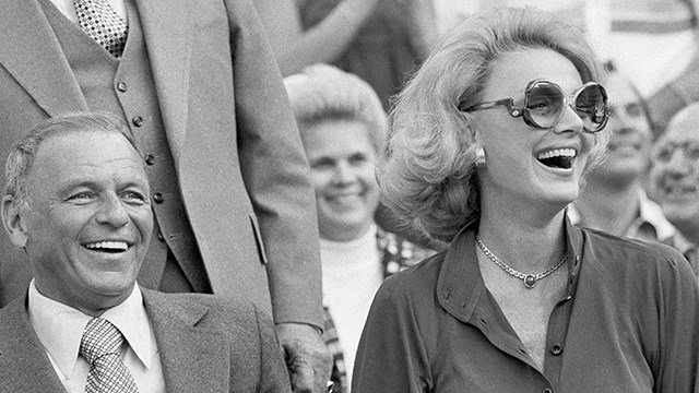 Frank and Barbara Sinatra are all smiles as they get set to watch the third game of the World Series in Los Angeles, Friday, Oct. 14, 1977. (AP Photo)