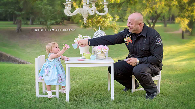 (Source: Cyndi Williams Photography, Coppell TX) Evelyn, now 1-year-old, reunited with Officer Diebold, who delivered her roadside, during a special tea party photo shoot one year after their first meeting in a gas station parking lot.