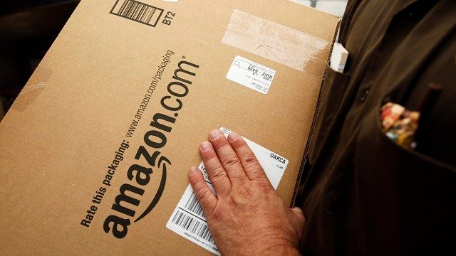 In this Oct. 18, 2010 file photo, an Amazon.com package is prepared for shipment by a United Parcel Service driver in Palo Alto, Calif. (AP Photo/Paul Sakuma, File)