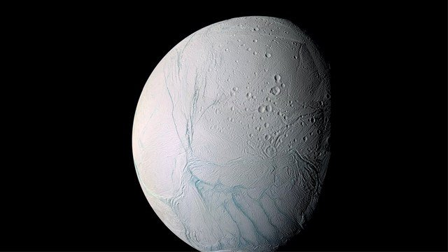 """An ocean at least as large as Lake Superior lies below a thick layer of ice on Enceladus, a moon of Saturn. Long """"tiger stripe"""" fractures appear in this picture of Enceladus. (File Photo)"""