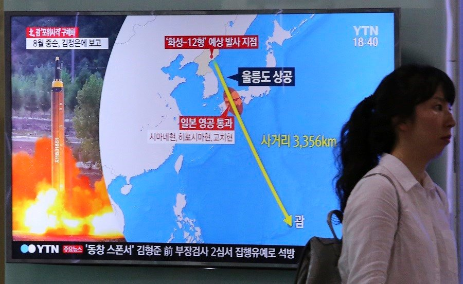 A woman passes by a TV screen showing a local news program reporting on North Korea's threats to strike Guam with missiles at the Seoul Train Station in Seoul, South Korea. (AP Photo/Ahn Young-Joon)