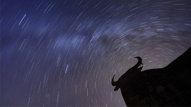In this photo taken with long exposure, stars and Perseid meteors streak across the sky during the annual Perseid meteor shower above a silhouette of a roadside billboard of a Spanish fighting bull. (AP Photo/Daniel Ochoa de Olza)