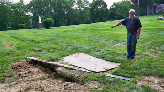 (James Keivom/The Daily News via AP). This Thursday Aug. 10, 2017 photo shows Mount Holiness Memorial Park caretaker Bill Plog as he stands by the burial plot of Cleveland Butler, in Butler, N.J. The New York Daily News reported the burial uncovered a ...