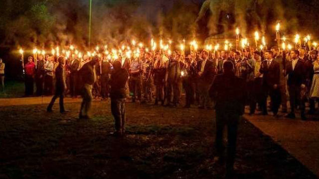 (Source: CNN) Torch-carrying demonstrators gather in Charlottesville on Saturday to protest the statue's removal.