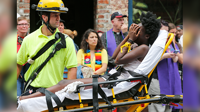 (AP Photo/Steve Helber) Rescue personnel help an injured woman after a car ran into a large group of protesters after an white nationalist rally in Charlottesville, Va., Saturday, Aug. 12, 2017