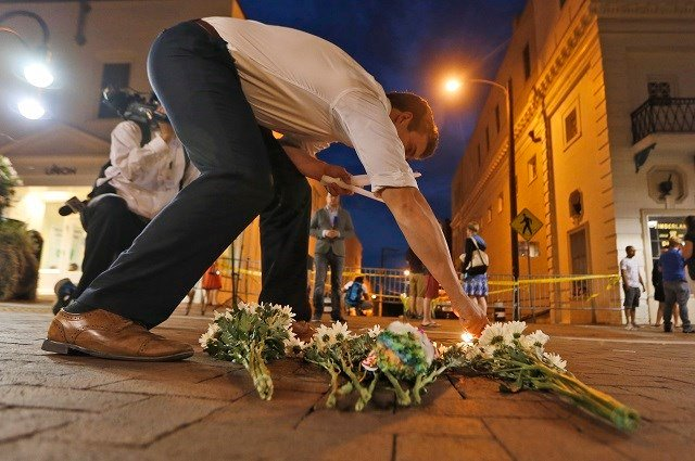 Charlottesville resident Elliot Harding lights a candle as he places flowers and a stuffed animal at a makeshift memoriall. (Source: AP Photo/Steve Helber)
