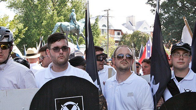 In this Saturday, Aug. 12, 2017 photo, James Alex Fields Jr., second from left, holds a black shield in Charlottesville, Va., where a white supremacist rally took place. (Alan Goffinski via AP)