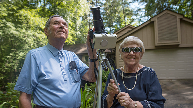(Ken Scar/Clemson University via AP) In this photo provided by Clemson University, Donald and Norma Liebenberg stand in the driveway of their home in Salem, S.C., on Thursday, Aug. 17, 2017.