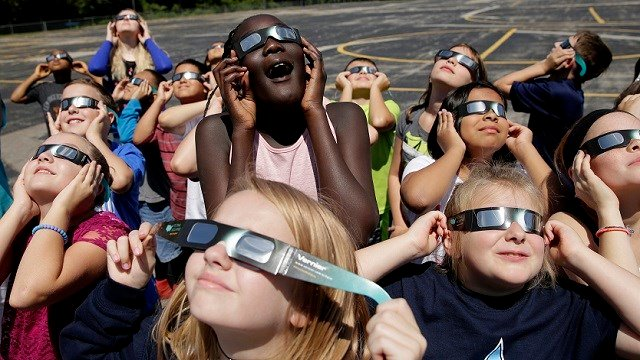 In this photo taken Friday, Aug. 18, 2017, fourth graders at Clardy Elementary School in Kansas City, Mo. practice the proper use of their eclipse glasses in anticipation of Monday's solar eclipse.  (AP Photo/Charlie Riedel)