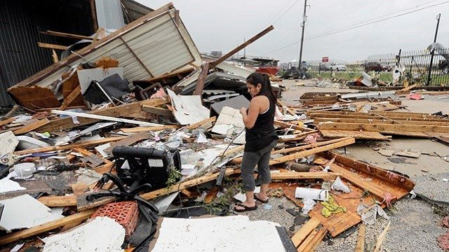 Jennifer Bryant looks over the debris from her family business destroyed by Hurricane Harvey Saturday, Aug. 26, 2017, in Katy, Texas.  (AP Photo/David J. Phillip)