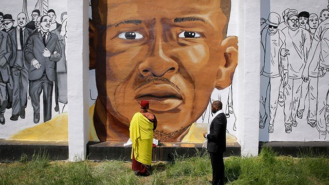 The Gyalwang Drukpa, bottom center, the Buddhist leader of South Asia, prays in front of a mural depicting Freddie Gray alongside the Rev. Jamal Bryant during a walking tour with other faith and community leaders. (AP Photo/Patrick Semansky)