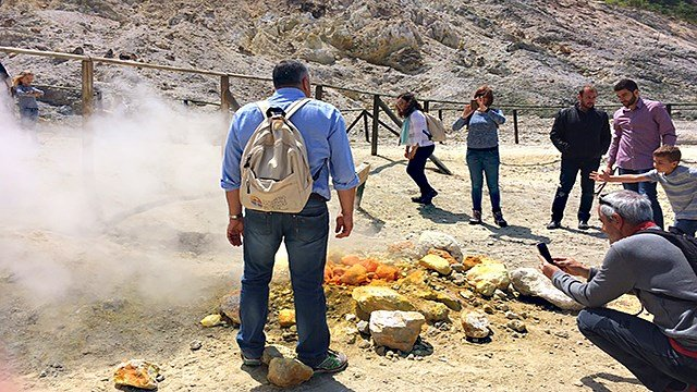In this photo taken on Saturday, April 30, 2016, visitors look at steaming fumarolas at the Solfatara crater bed, in the Phlegraean Fields near Naples, Italy. (AP Photo/Frances D'Emilio)