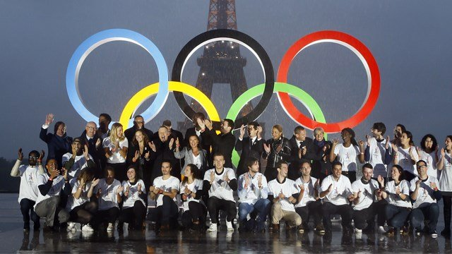 Paris officials pose in front of a display showing the Olympic rings on Trocadero plaza that overlooks the Eiffel Tower, as they celebrate the vote in Lima, Peru, awarding the 2024 Games to the French capital, in Paris. (AP Photo/Francois Mori)