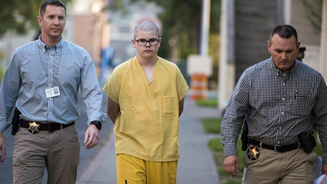 (Colin Mulvany/The Spokesman-Review via AP) In this Wednesday, Sept. 13, 2017 photo, Spokane County Sheriff's deputies escort Caleb Sharpe from the Public Safety Building to the Juvenile Detention Center in Spokane, Wash.