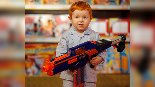 (AP Photo/Frank Augstein) Two year old Tristan poses with the new Nerf Rapid Strike during a preview presentation of Christmas Toys at the toy store Hamleys in London, Thursday, June 27, 2013.