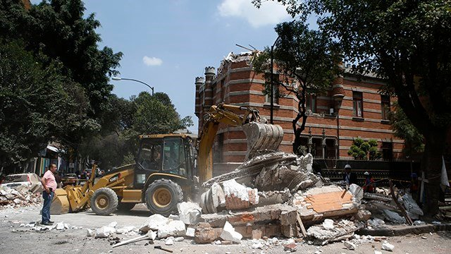 A bulldozer removes debris from a partially collapsed building after an earthquake in Mexico City, Tuesday. (AP Photo/Rebecca Blackwell)