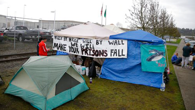 (AP Photo/Ted S. Warren, File). FILE - In this April 12, 2017, file photo, students and other immigration-rights supporters gather outside tents by the Northwest Detention Center in Tacoma, Wash. Washington state on Wednesday, Sept. 20, sued the operat...