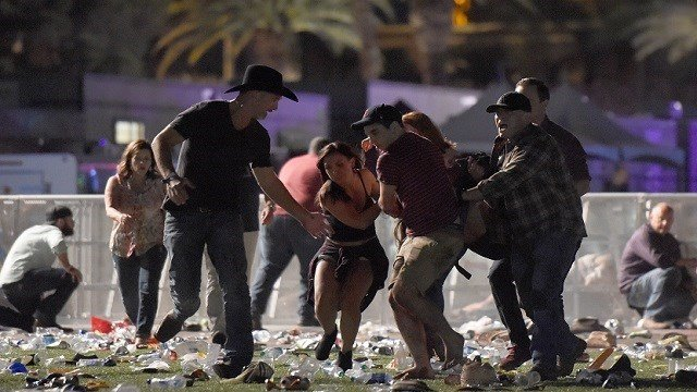 People carry a peson at the Route 91 Harvest country music festival after apparent gun fire was heard on October 1, 2017 in Las Vegas, Nevada. There are reports of an active shooter around the Mandalay Bay Resort and Casino. (Photo by David Becker/Getty)