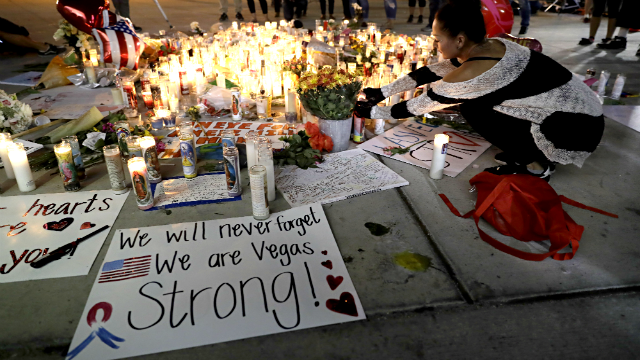 A woman places a candle at a memorial for victims of the mass shooting Tuesday, Oct. 3, 2017, in Las Vegas. (AP Photo/Marcio Jose Sanchez)