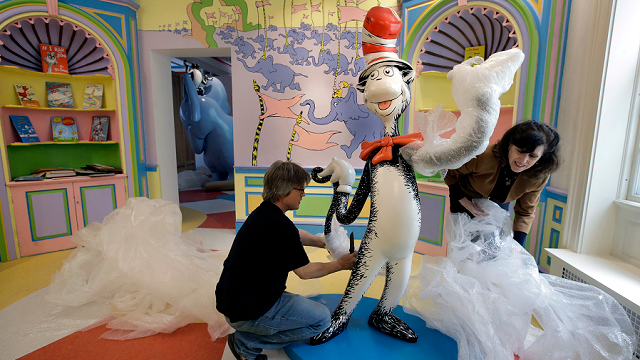"In this May 4, 2017, photo John Simpson, left, project director of exhibitions for The Amazing World of Dr. Seuss Museum unwraps a statue of the ""Cat in the Hat,"" at the museum, in Springfield, Mass. AP Photo/Steven Senne)"