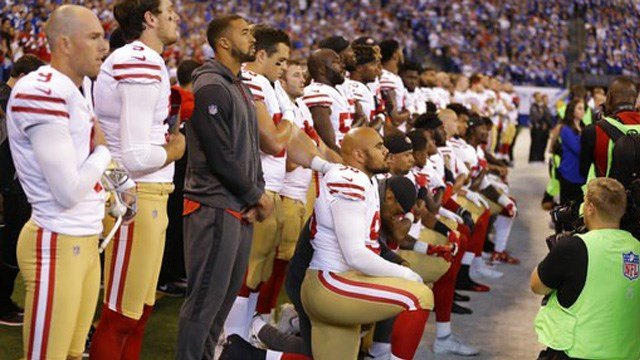 (AP Photo/Michael Conroy). Members of the San Francisco 49ers kneel during the playing of the national anthem before an NFL football game against the Indianapolis Colts, Sunday, Oct. 8, 2017, in Indianapolis.