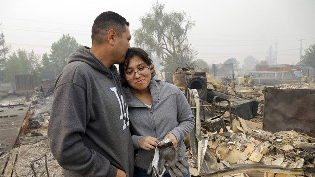 Jose Garnica, left, kisses his daughter Leslie Garnica in front of their home that was destroyed in the Coffey Park area of Santa Rosa, Calif., on Tuesday, Oct. 10, 2017. (AP Photo/Ben Margot)
