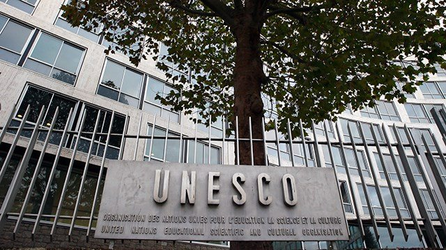 In this Monday Oct. 17, 2016 file picture, the United Nations Educational Scientific and Cultural Organization logo is pictured on the entrance at UNESCO's headquarters in Paris. (AP Photo/Francois Mori, File)