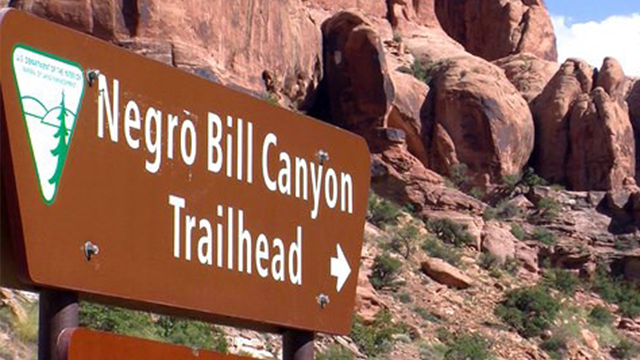 (John Hollenhorst /The Deseret News via AP, File). FILE - This undated file photo shows a sign at the entrance of the Negro Bill Canyon Trailhead in Moab, Utah. After years of debate, a U.S. government board has voted unanimously to rename Utah's Negro...