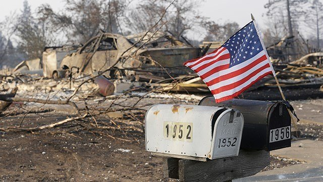 A small flag attached to mail boxes flies in front of homes destroyed by fires in Santa Rosa, Calif., Wednesday, Oct. 11, 2017.  (AP Photo/Jeff Chiu)
