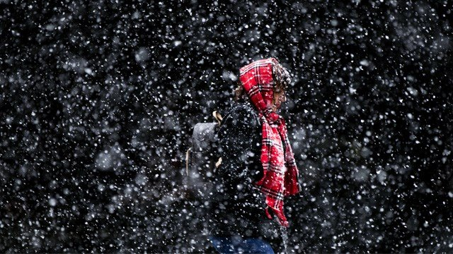 In this March 10, 2017 file photo, a woman walks through a winter snow storm in Philadelphia. In a report released Thursday, Oct. 19, U.S. forecasters say chances are good that much of the nation will have a warmer than normal winter. (Photo: Matt Rourke)
