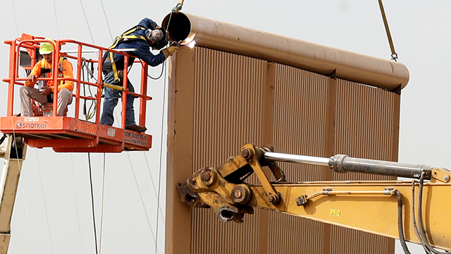 Crews work on a border wall prototype near the border with Tijuana, Mexico, Thursday, Oct. 19, 2017, in San Diego. Companies are nearing an Oct. 26 deadline to finish building eight prototypes of President Donald Trump's proposed border wall with Mexico.