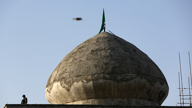 An Afghan soldier left, stands guard on the roof of a Mosque near to the site of suicide attack In Kabul near Afghanistan's Defense Ministry, Monday, Sept. 5, 2016. (AP Photo/Rahmat Gul)