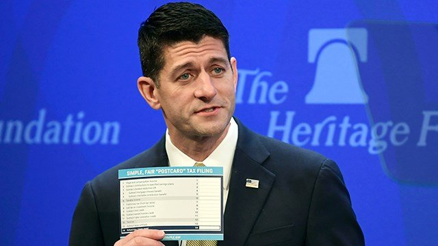 """House Speaker Paul Ryan of Wis., holds up a copy of a proposed """"simple tax"""" postcard while speaking at the Heritage Foundation in Washington, Thursday, Oct. 12, 2017. (AP Photo/Susan Walsh)"""