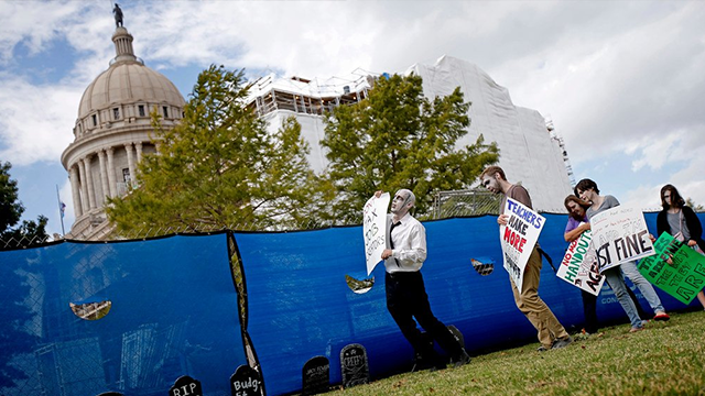 People dressed as zombies film a short movie for Together Oklahoma in protest of the state's budget situation outside the state Capitol in Oklahoma City, Saturday, Oct. 21, 2017. (Bryan Terry/The Oklahoman via AP)