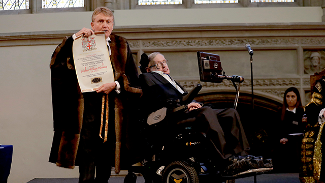 (AP Photo/Matt Dunham) Britain's Professor Stephen Hawking is presented with his illuminated Freedom scroll by the Chamberlain of the City of London Peter Kane as he receives the Honorary Freedom of the City of London during a ceremony at the Guildhall...