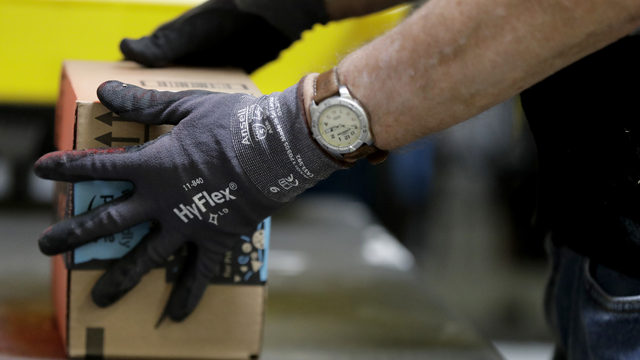 An employee packages a product at the Amazon Fulfillment center in Robbinsville Township, N.J., Tuesday, Aug. 1, 2017. Amazon held a nation-wide job fair at its warehouses on Aug. 2. (AP Photo/Julio Cortez)