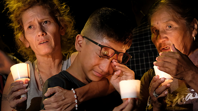 Mona Rodriguez, Jayanthony Hernandez, 12 and Juanita Rodriguez, from left, participate in a candlelight vigil held for the victims of a fatal shooting at the First Baptist Church of Sutherland Springs. (AP Photo/Laura Skelding)